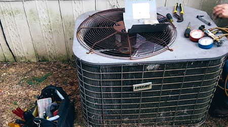 In this image, we see an older air conditioning system that is completely broken down and needs replacing